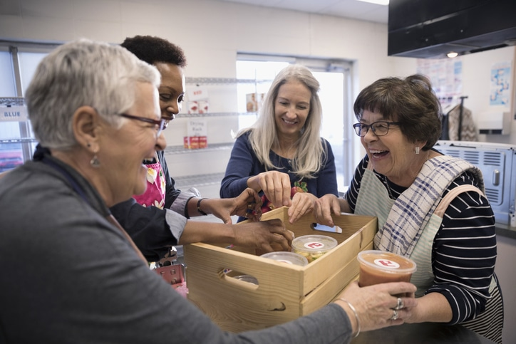 Female Volunteers Packing Soup Containers Into Crate In Soup Kitchen