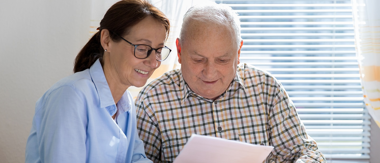 Caregiver and elderly man reading paperwork